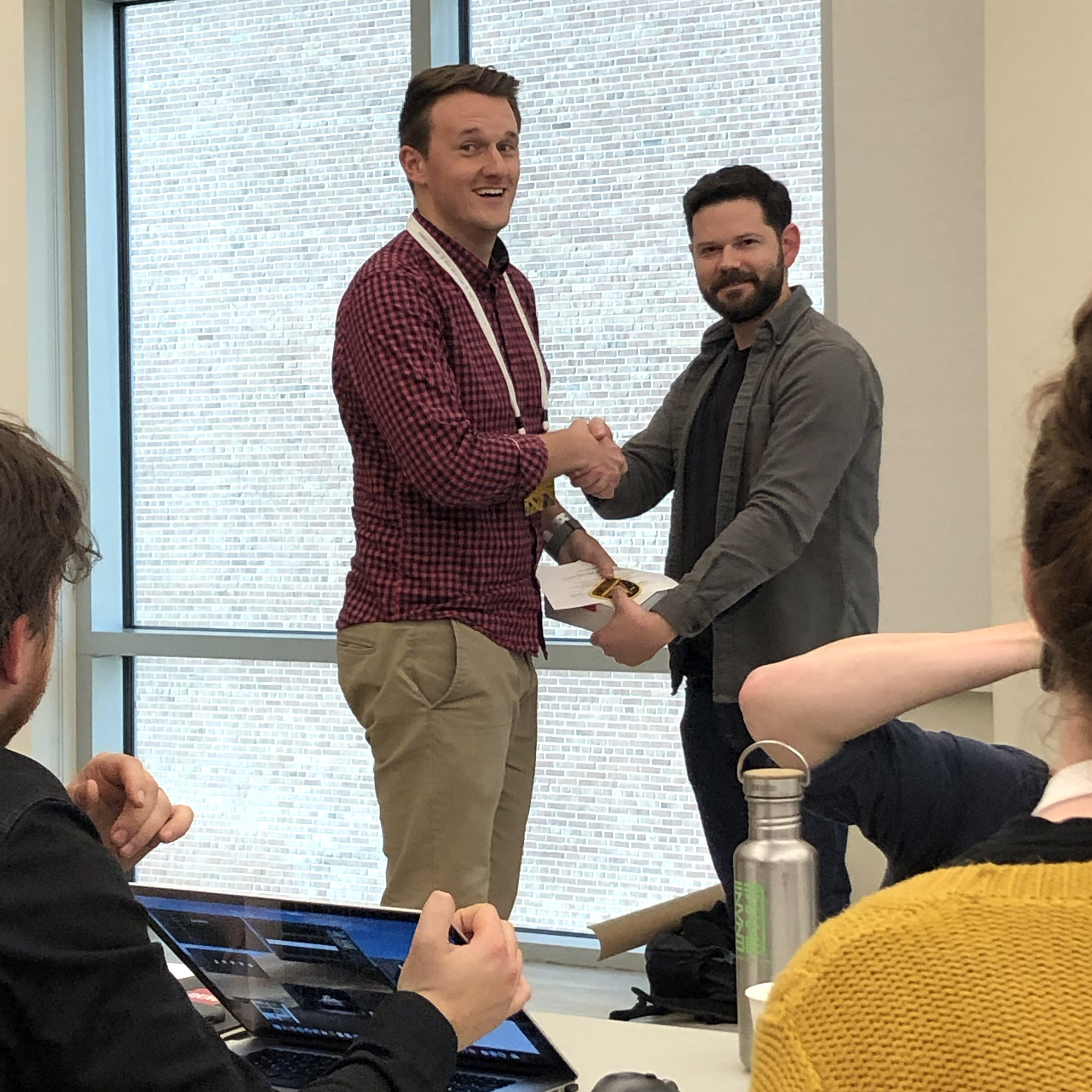 Austin and Nathan shaking hands at a playful, low-key course completion ceremony